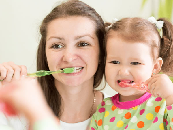 mother and daughter brushing there teeth